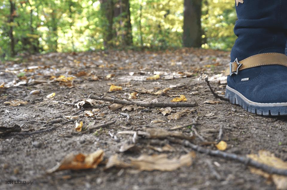 Nahaufnahme ines Kinderstiefels auf Waldboden