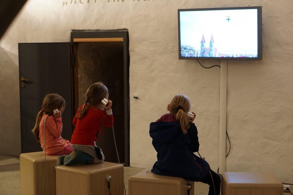 Drei Kinder sehen einen Infofilm