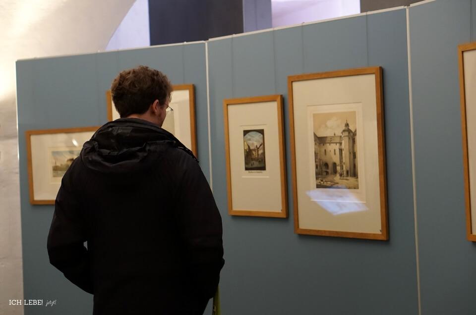 Ein Mann betrachtet die Bilder der Cadolzburg im Wandel der zeit.
