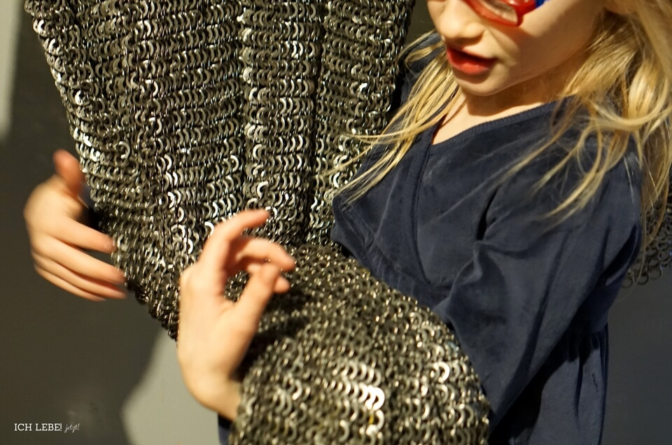Die Sechsjährige hebt das schwere Kettenhemd