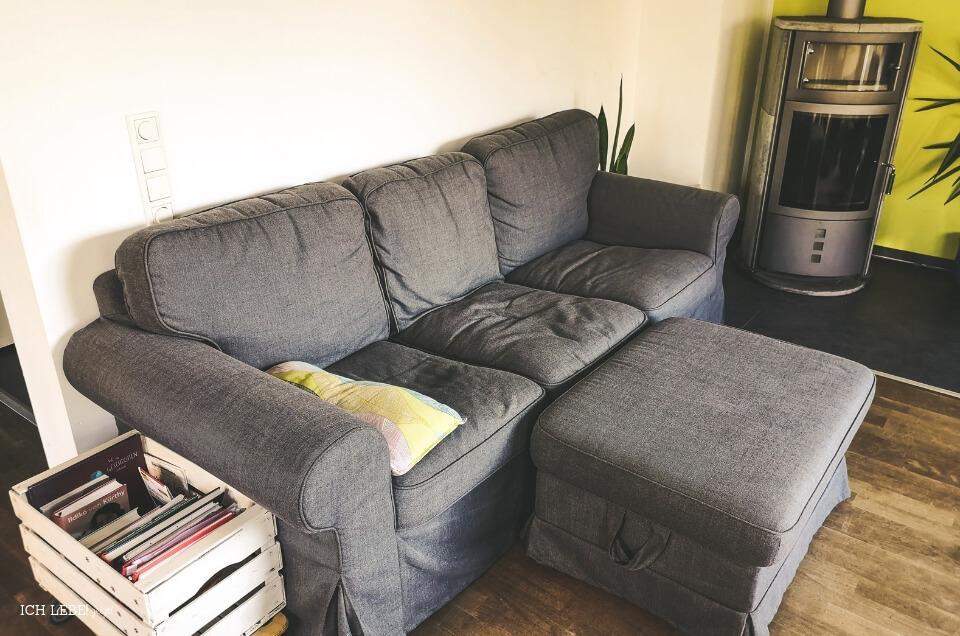 Sofa neben Bücherkiste und Kaminofen
