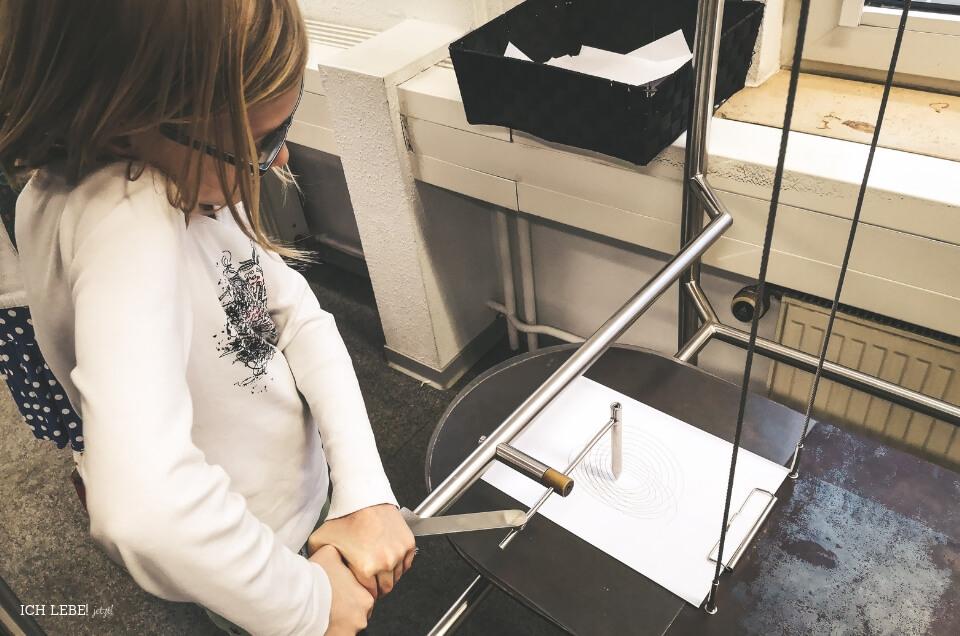 Stift der an einem Pendel befestigt ist malt eine Grafik.