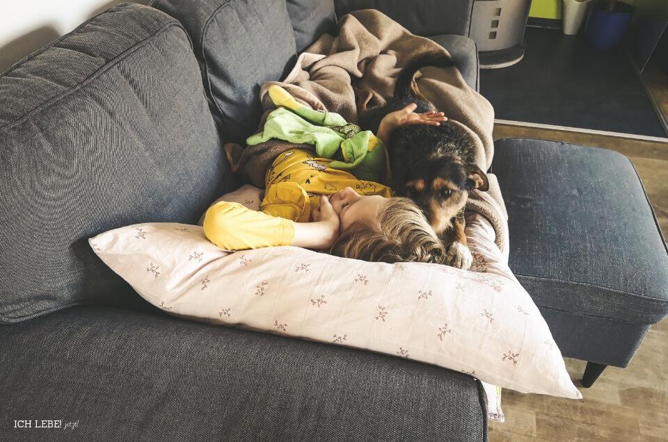 Kind auf dem Sofa mit Hund