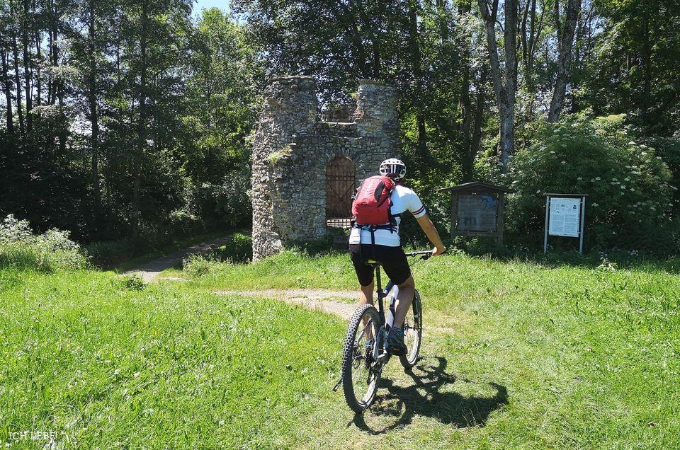 Fahrradfahrer von hinten vor der Burgruine Kalden