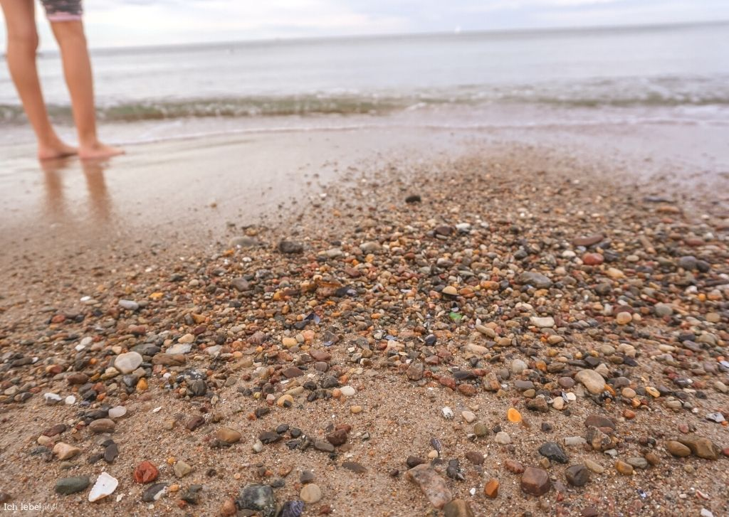 Bunter Strand mit den Füßen im Wasser
