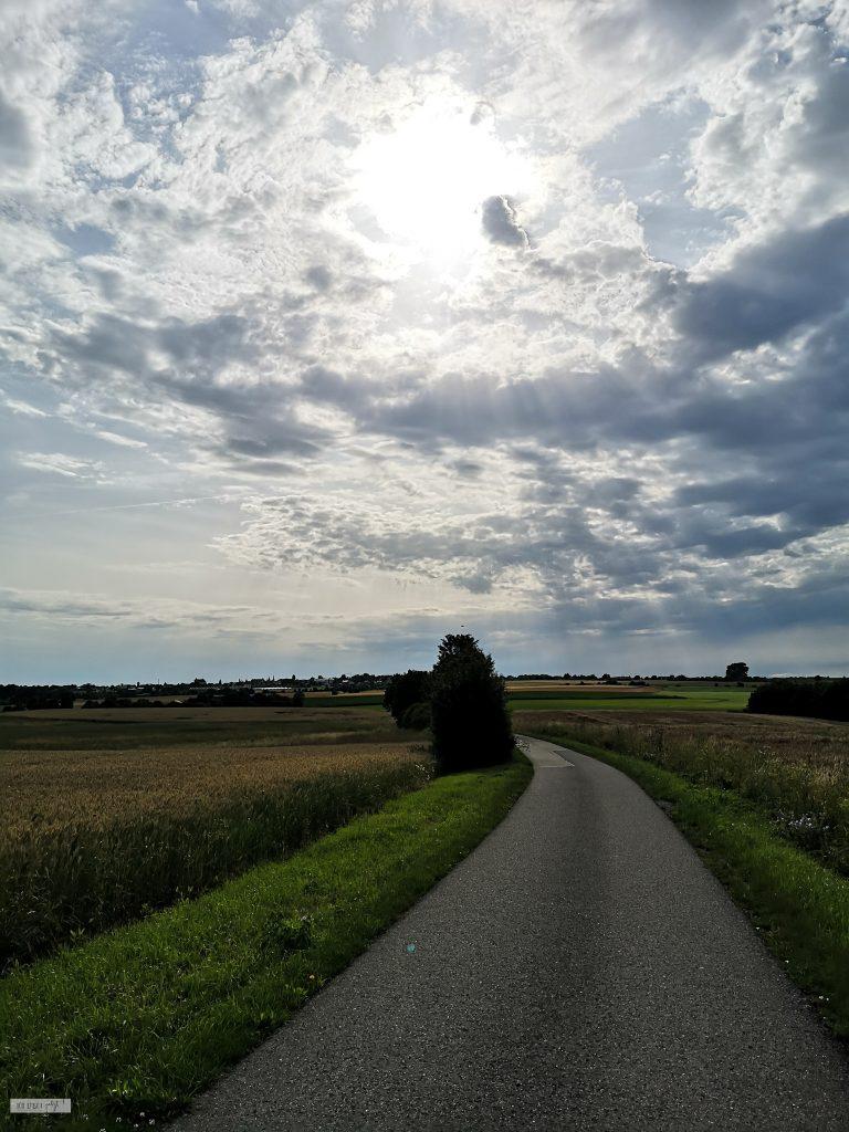 Straße und von der Sonne beschienener, wolkiger Hinmel